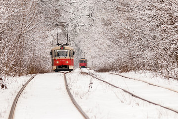 An old tram moving through a winter forest