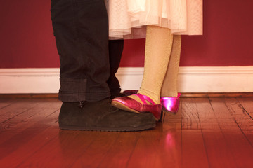 daughter dancing on father's feet in formal wear