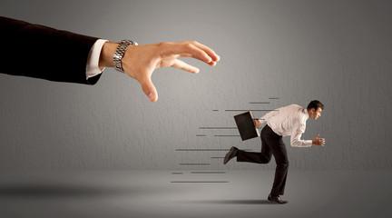 Businessman running away from a huge hand
