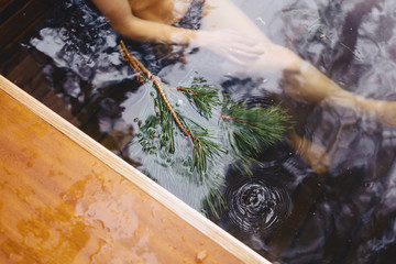 Pine branches near a hot conifer in a water of hot tube spa