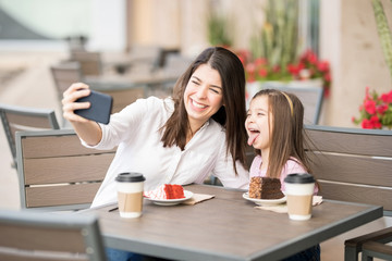 Cheerful mother and daughter at cafe taking selfie