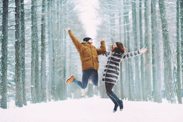 Guy and girl walk ,have fun in the forest in winter