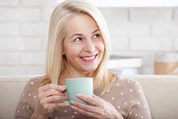 Portrait of happy blonde with mug in hands. Cup of coffee in the morning