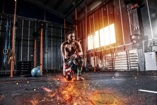 Athletic boy works out at the gym with a fiery kettlebell