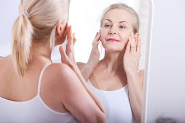 Middle aged woman looking at wrinkles in mirror. Plastic surgery and collagen injections. Makeup. Macro face. Selective focus