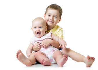 Portrait of kid brother hugging his little cute sister sitting on floor isolated on white background
