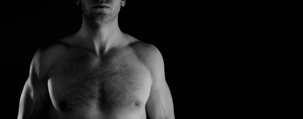 Torso of a male athlete on a black background