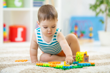 toddler boy playing indoors with educational toy sitting on soft carpet