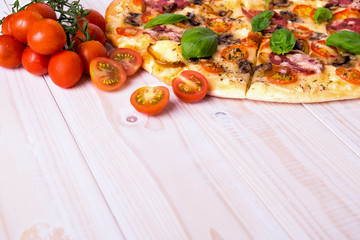Pizza with Salami Vegetables and Spices on a white wooden background with copy space.