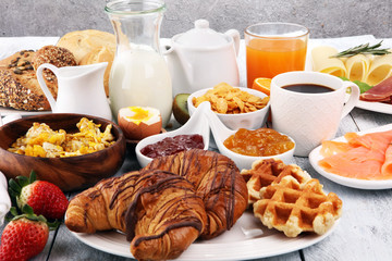 breakfast on table with waffles, croissants, coffe and juice