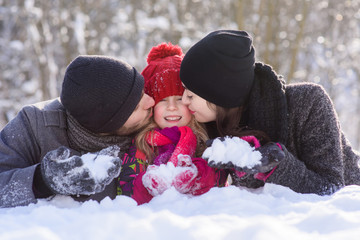 Happy family laying on snow outdoors