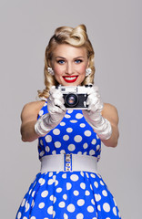 woman, with no-name camera, taking picture, dressed in pin-up style