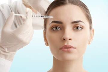 Woman at plastic surgery. Portrait of an attractive young woman receiving botox treatment. Isolated on light blue background.
