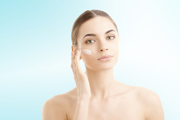 Studio shot of beautiful young woman applying moisturizer cream onto her face against at isolated light blue background with copy space.
