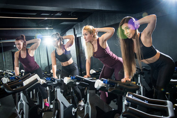 Group of attractive slim young women training on exercise bikes together at gym.