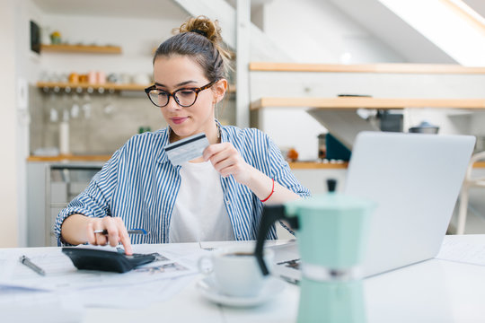 Young woman paying bills online with credit card