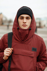 Street portrait of a fashionable guy in a stylish red jacket with a hood with a black hat and a backpack in the city