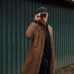 Handsome young man in a fashion coat with a cap on the street near the green wall
