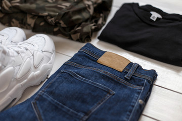 Men's summer collection of fashion clothes on a white wooden background. Sneakers, T-shirt, military cloth and jeans