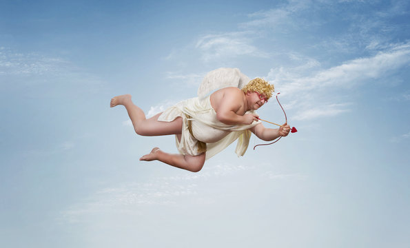 Funny overweight cupid aiming with the arrow of love over clear blue sky with copy space