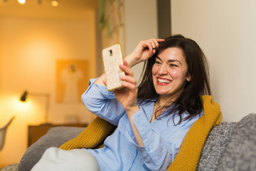 Selfie time. Woman aitting on sofa in her living room and  taking selfie.