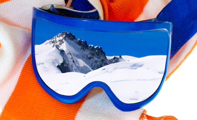 Ski goggles with reflection of a snowy mountain scene. Orange and white striped scarf background.