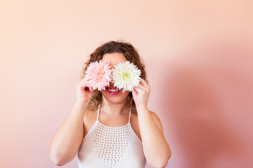 Beautiful curly woman holding two flowers, pink and white on color background at home. Hello Spring concept.
