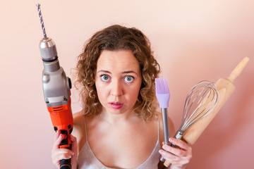 Beautiful curly woman holding man driller and kitchen tools. Gender equality, women's day concept.