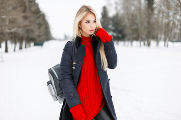 Pretty stylish young woman in a trendy fashion coat with a red sweater with a stylish bag walks