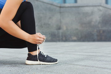 Woman tying shoes laces before running