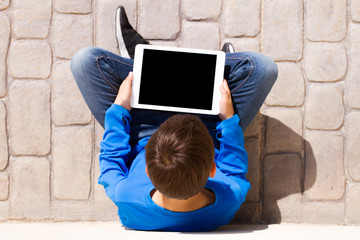 Child with tablet computer sitting outdoors. Top view.