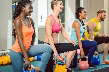 Gruppe von Männern und Frauen bei Fitness Training mit Kettlebell