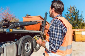 Bauarbeiter auf Baustelle lädt Bauschuttcontainer ab mit Fernbedienung