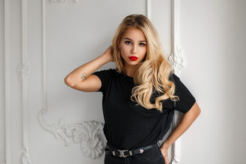 Stylish pretty young woman in a fashion black T-shirt near a white wall