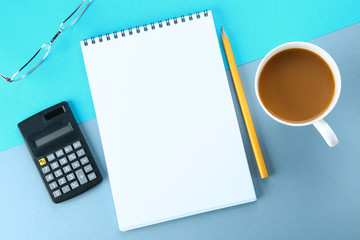 Top view image of open notebook with blank pages and coffee on blue background, ready for adding or mock up. Still life, business, office supplies or education concept.