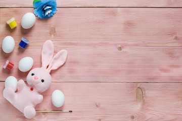 Easter festive set with eggs, flower and easter rabbit, paint, brush on rustic wooden table with copyspace. Flat lay, space for mock up and copy space. Top view.