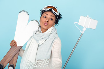 Young african woman isolated on blue wall studio winter sport skiing taking photos