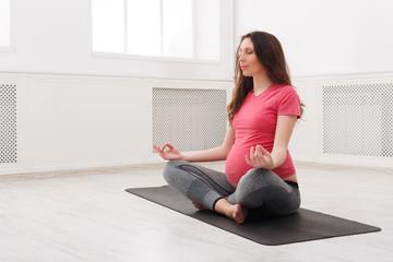 Pregnant woman meditating at home
