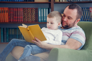 Image of father reading book to son sitting in chair