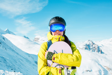 Picture of sporty woman wearing helmet and snowboarding against background of snowy hills