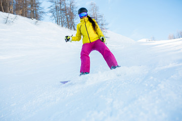 Image of sports woman in helmet and snowboarding mask from snowy slope with trees