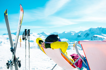 Picture from back of woman in armchair, skis, sticks in snowy resort