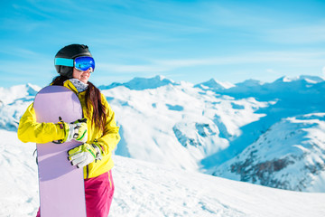Picture of smiling brunette in helmet and mask with snowboard on background of snowy hills