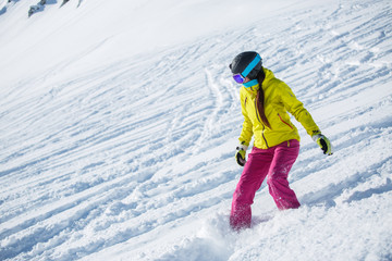 Image of brunette athlete wearing helmet and mask, snowboarding from snowy mountain slope