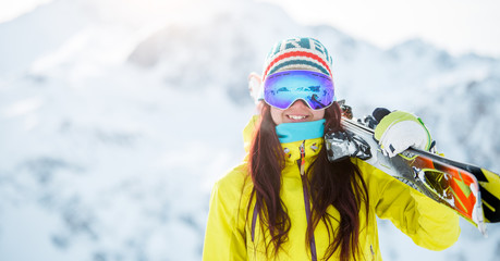 Image of woman with skis on her shoulder in background of snowy hill