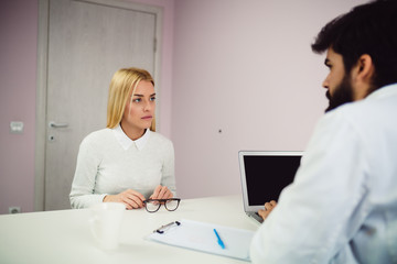 Female patient talking with handsome doctor in his office.