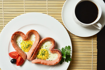 Scrambled eggs in the form of heart on a white plate with sausages, tomatoes, greens and coffee with lemon.