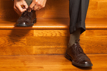 Man in a business suit ties his shoe lace
