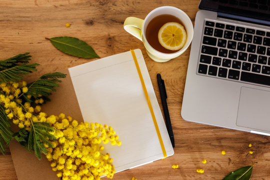 cup of tea notebook, laptop, flowers on a wooden background