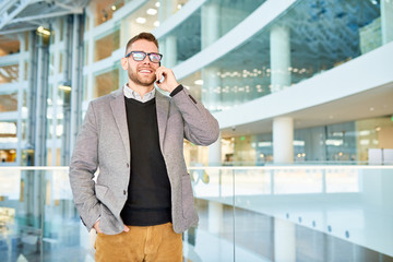Portrait of cheerful modern businessman speaking by phone and smiling while standing at glass balcony in office center, copy space